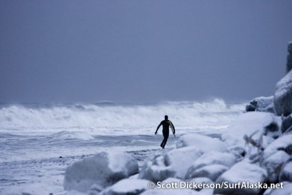 Gart Curtis runs towards some gnarly winter storm surf in Alaska.