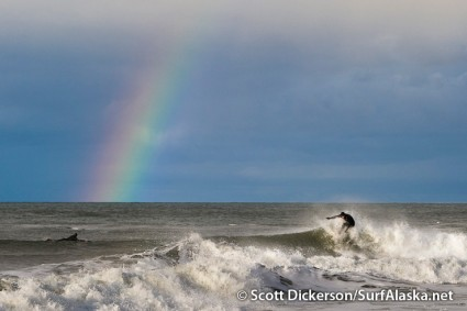 Jake Beaudoin surfing with a rainbow on Cook Inlet, Alaska