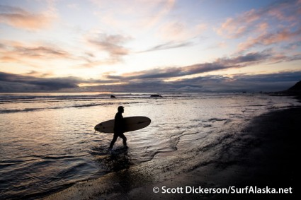 Iceman walking out of the sunset after surfing Snappers, Yakutat, Alaska