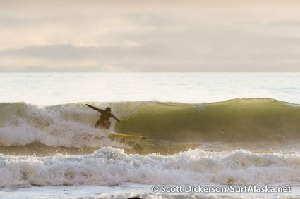 Mike McCune dropping into a glassy backlit beach break barrel.