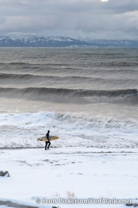 Alaskan surfer, Jake Beaudoin, walks the snowy beach for another drift down current.