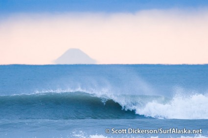 Surf wave with Augustine Volcano in the distance.