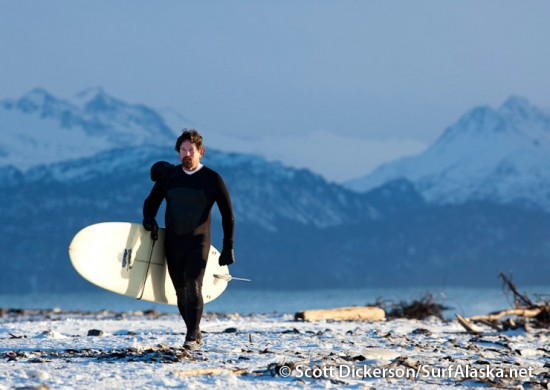 Alaskan surfer, Ty Gates walking out of winter scene.
