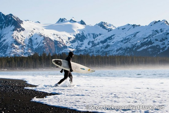 Alex Wilson heading out for a surf with the Kenai Mountain Range setting the scene.