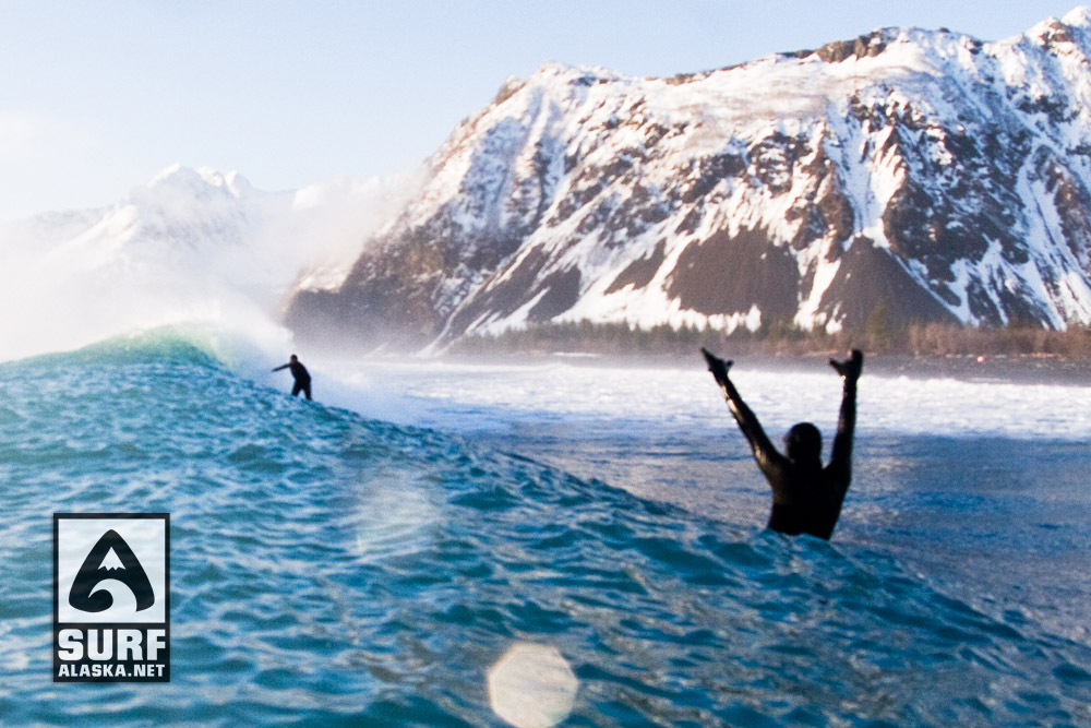 A surfer rides a wave as another surfer cheers him on during win