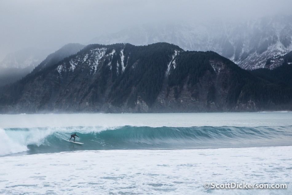 Surfing a barreling wave in Alaska. Snowy mountains in the background.
